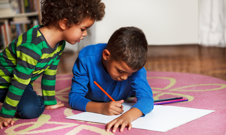 Cute school boys lying on the carpet, at home, drawing with crayons.