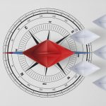 Concept vision leadership temwork and workforce leader management with red paper ship on compass needle pointing in front of leading among paper ship white.