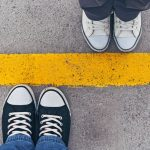 Sneakers from above. Male and female feet in sneakers from above, standing at dividing line.