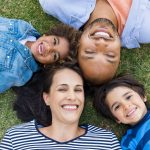 Overhead view of cheerful family lying on grass in a circle and looking at camera. High view of multiethnic family lying on grass at park. African father and hispanic mother with their smiling children
