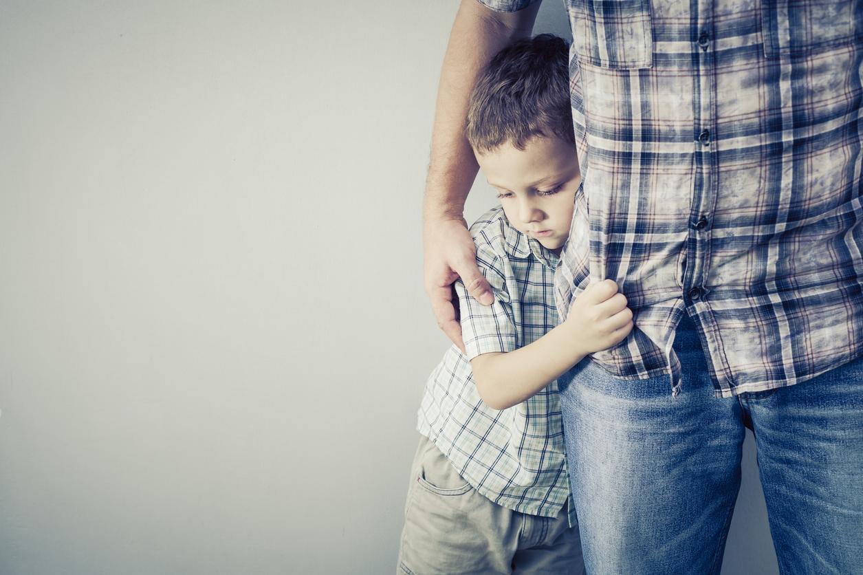 sad son hugging his dad near wall at the day timesad son hugging his dad near wall at the day time