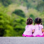 Rear view of two little girl sitting on ground at park